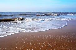 Rolling waves on the Dutch coast. Foamy surf with rolling waves on the Dutch North-sea coast with blue sky Stock Photos