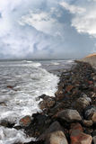 Rolling waves on pebbled coastline Stock Images