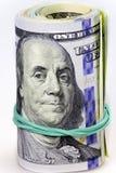 Rolll av dollarräkningar som isoleras på vit Arkivfoto