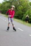 Rolller de la niña que patina en un parque Fotografía de archivo