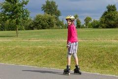 Rolller de la niña que patina en un parque Foto de archivo libre de regalías