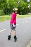 Rolller de la niña que patina en un parque Imágenes de archivo libres de regalías