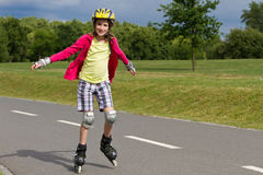Rolller de la niña que patina en un parque Fotos de archivo libres de regalías