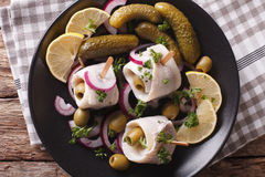Rollmops herring with olives, onions and pickles close up. Horiz Stock Photo