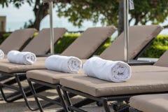 Rollo blanco de la toalla en sunbeds en la piscina foto de archivo
