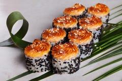Rollo cocido con las semillas de sésamo y el sombrero negro, hojas tropicales, aún vida, cocina japonesa Fotos de archivo libres de regalías