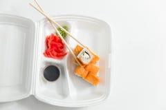 Rollo con los palillos, rollos, sushi sushi y palillos de la entrega del envase Fotos de archivo libres de regalías