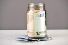 Rollo de billetes de banco euro en un tarro del dinero Imágenes de archivo libres de regalías