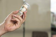 Rollo de 100 billetes de dólar en una mano del ` s del hombre Fotos de archivo