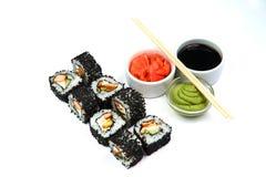 Rollo de California negro con la salsa de soja, el wasabi, el jengibre y los palillos en el fondo blanco Comida japonesa imagen de archivo