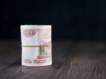 Rollo de cinco milésimas notas de las rublos sobre fondo de madera Foto de archivo libre de regalías