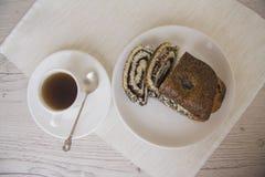 Rollo de la amapola y taza de café hechos en casa Imagen de archivo