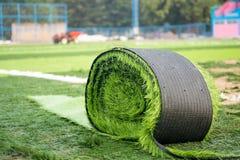 Rollo de la hierba artificial en nuevo campo de fútbol imagenes de archivo