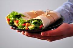 Rollo de la tortilla con el pollo, la pimienta roja, el pepino, y la lechuga asados a la parrilla en la mano de un adolescente Imagenes de archivo