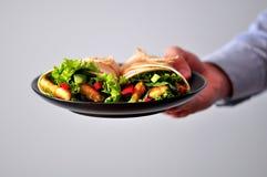 Rollo de la tortilla con el pollo, la pimienta roja, el pepino, y la lechuga asados a la parrilla en la mano de un adolescente Fotos de archivo