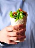 Rollo de la tortilla con el pollo, la pimienta roja, el pepino, y la lechuga asados a la parrilla en la mano de un adolescente Fotos de archivo libres de regalías
