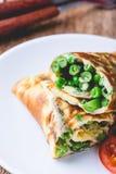 Rollo de la tortilla del huevo con el relleno de las habas verdes y de los guisantes Fotos de archivo libres de regalías