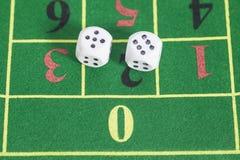 Rollo de los dados blancos en la mesa de juegos Foto de archivo libre de regalías