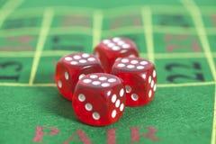 Rollo de los dados rojos en la mesa de juegos Foto de archivo libre de regalías