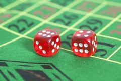 Rollo de los dados rojos en la mesa de juegos Fotografía de archivo