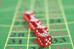 Rollo de los dados rojos en una mesa de juegos Imagen de archivo libre de regalías