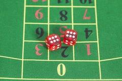 Rollo de los dados rojos en una mesa de juegos Fotografía de archivo