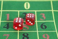 Rollo de los dados rojos en una mesa de juegos Fotografía de archivo libre de regalías
