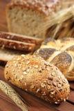 Rollo de pan completo del grano en la tabla de madera con el oído del centeno imagen de archivo libre de regalías