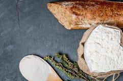 rollo de pan o baguette y harina franceses en negro Imagenes de archivo