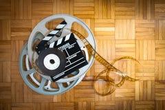 Rollo de película del tablero y de chapaleta de la película en piso de madera Foto de archivo libre de regalías