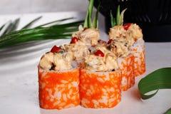 Rollo de sushi caliente, apetitoso, grande, de color salmón, anaranjado, salsa, kimchi, sésamo, ahumado, pepino, tropical, palma  Imagenes de archivo