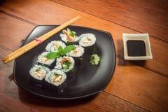 Rollo de sushi con el atún y el pepino en la placa negra imagenes de archivo