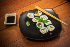 Rollo de sushi con el atún y el pepino en la placa negra imagen de archivo libre de regalías