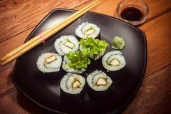 Rollo de sushi con el pollo y la lechuga en la placa negra imágenes de archivo libres de regalías