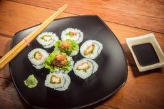 Rollo de sushi con el pollo y la lechuga en la placa negra foto de archivo libre de regalías