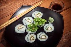 Rollo de sushi con el pollo y la lechuga en la placa negra foto de archivo