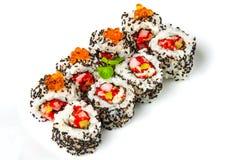 Rollo de sushi con el sésamo del camarón, de las huevas del pez volador, de color salmón y negro Imagenes de archivo