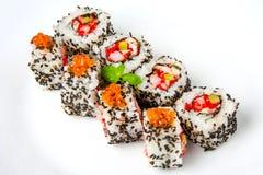 Rollo de sushi con el sésamo del camarón, de las huevas del pez volador, de color salmón y negro Foto de archivo