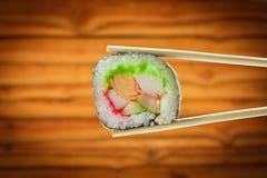 Rollo de sushi con los palillos sobre el fondo de madera Fotografía de archivo libre de regalías