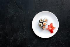Rollo de sushi con los salmones y el aguacate en la placa en copyspace negro de la opinión superior del fondo Fotografía de archivo
