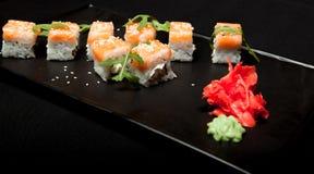 Rollo de sushi con los salmones y el aguacate en la placa en la opinión superior del fondo negro Imagen de archivo