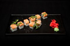 Rollo de sushi con los salmones y el aguacate en la placa en la opinión superior del fondo negro Imagen de archivo libre de regalías