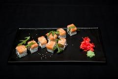 Rollo de sushi con los salmones y el aguacate en la placa en la opinión superior del fondo negro Imágenes de archivo libres de regalías