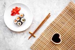 Rollo de sushi con los salmones y el aguacate en la placa con la salsa de soja, palillo, wasabi en la estera en la opinión superi Fotos de archivo libres de regalías