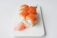 Rollo de sushi con los salmones y el queso de Philadelphia en el fondo blanco fotografía de archivo