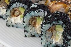 Rollo de sushi con tobiko rojo y rollo de sushi de Canadá con sésamo Foto de archivo libre de regalías