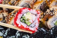 Rollo de sushi con tobiko rojo y rollo de sushi de Canadá con sésamo Imágenes de archivo libres de regalías