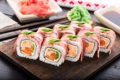 Rollo de sushi con tocino Imagenes de archivo