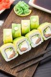 Rollo de sushi cubierto con el aguacate Imágenes de archivo libres de regalías