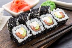 Rollo de sushi de color salmón cubierto con sésamo Imagen de archivo